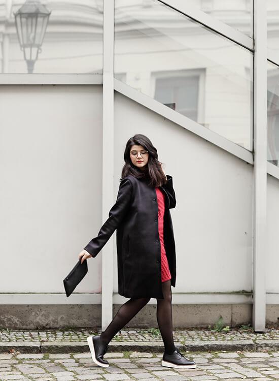 Frau in rotem Pulli und schwarzer Jeans