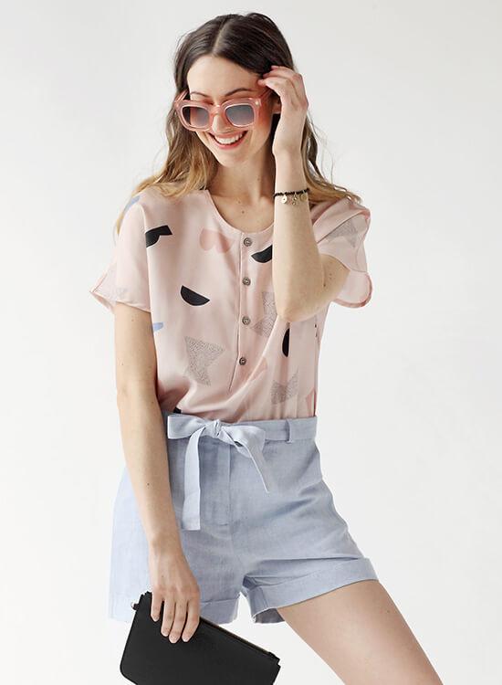 Frau in rosa Bluse und hellblauer Shorts