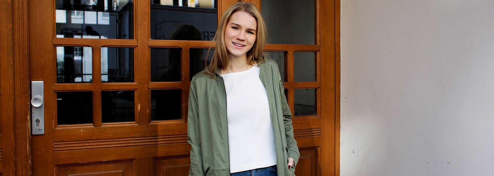 Frau mit weißem Pullover und grüner Jacke