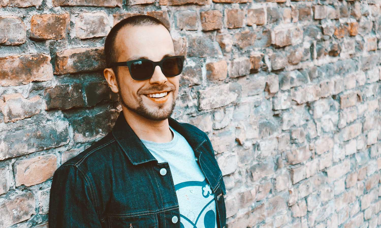 Mann mit Sonnenbrille lehnt sich gegen Hauswand