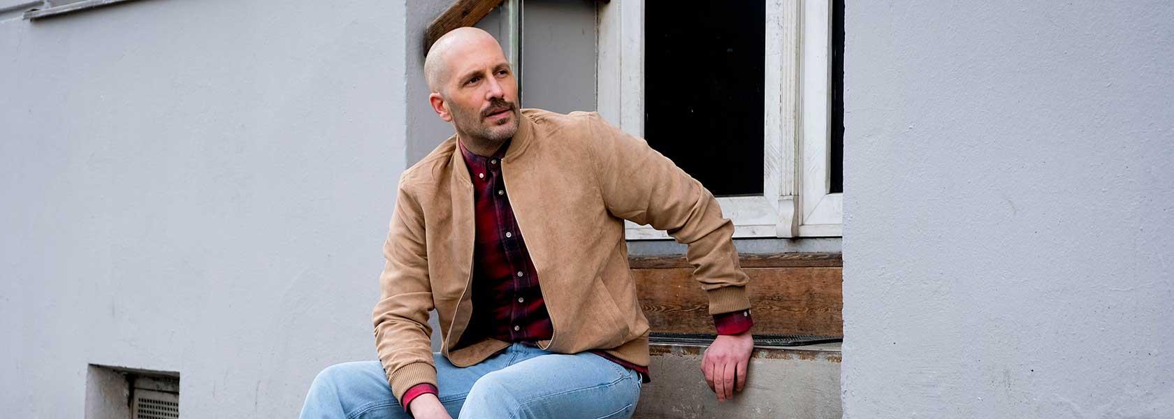 Mann in veganer Lederjacke lsitzt auf einter Treppe
