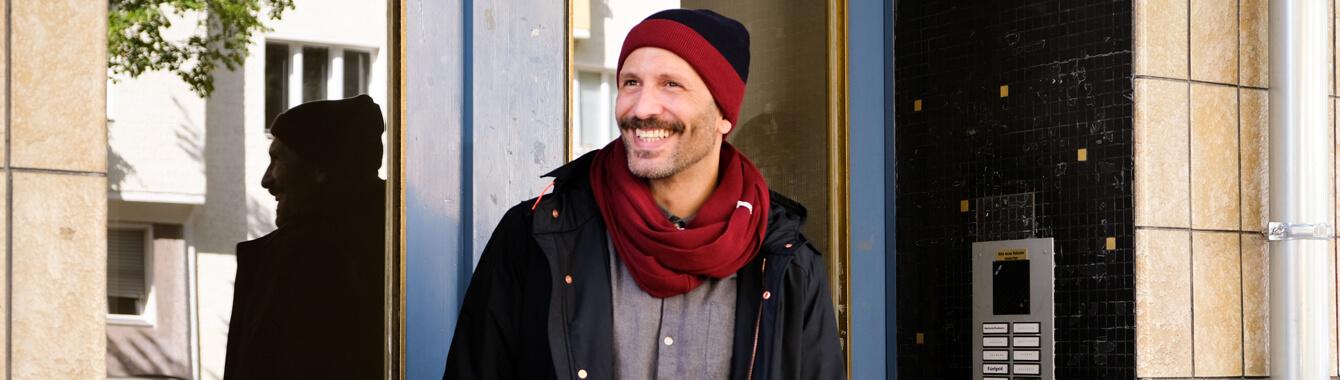 Mann trägt unsere liebsten Herbst Essentials: Strickmütze & Schal