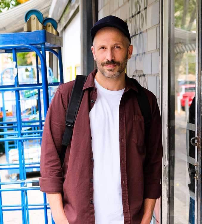 Mann mit offenem Hemd steht vor Kiosk