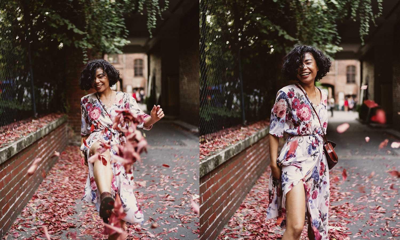 Frau in Blumenkleid tanz durch Laub