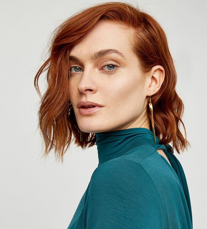 Frau trägt goldene Ohrringe