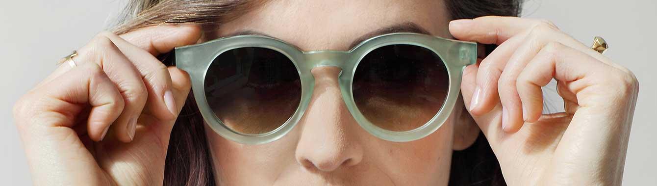 Sonnenbrille mit transparentem Rahmen liegt auf rotem Untergrund