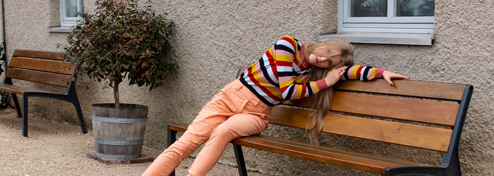 Frau in geringeltem Pullover und rosa Hose lehnt sich auf Holzbank