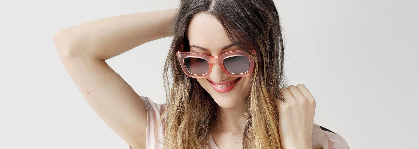 Frau mit rosa Brille und goldener Armkette