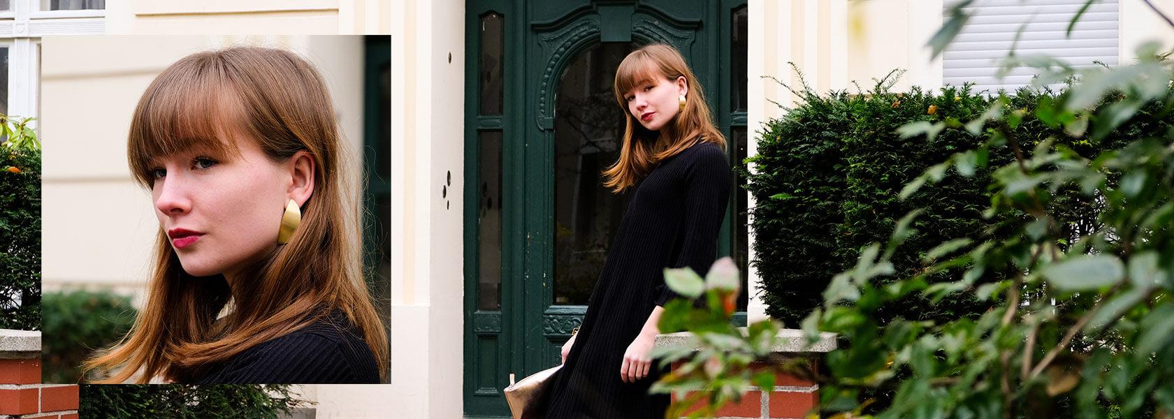Frau in schwarzem Kleid steht vor Haustür