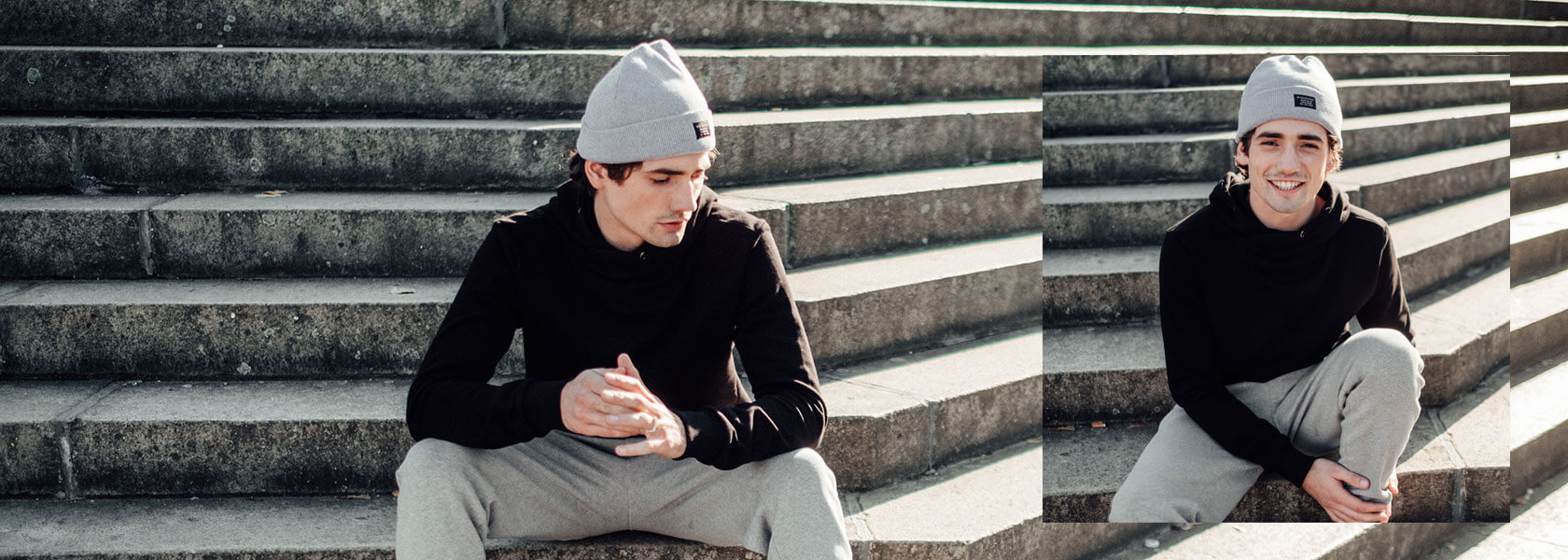 Mann in schwarzem Pullover sitzt auf einer Treppe