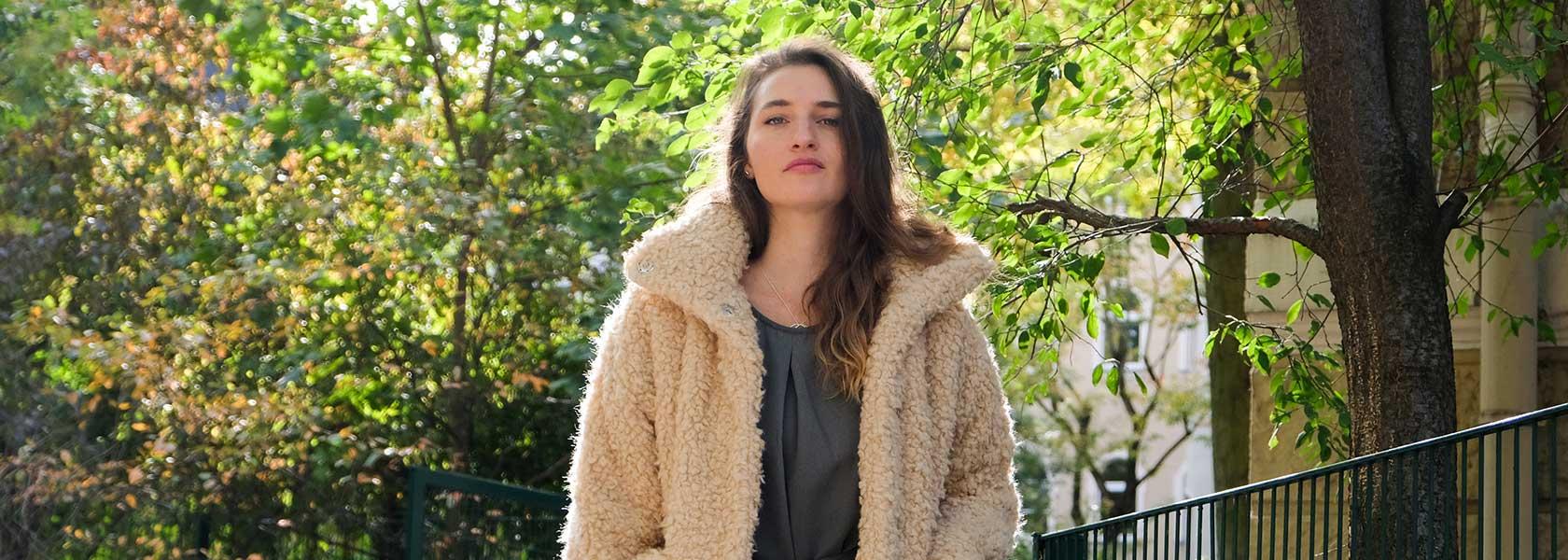 Frau in weißer Winterjacke steht im Park