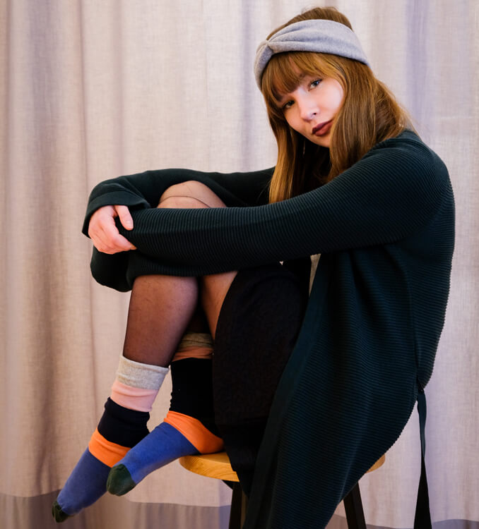 Frau trägt Strickjacke, Socken und ein Stirnband