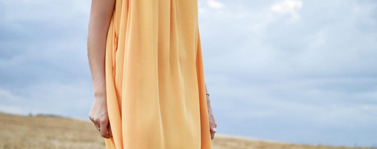 Frau in Kleid aus EcoVero auf Feld mit Himmel im Hintergrund