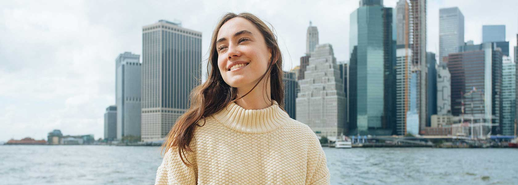 Frau in beigem Strickpullover vor New Yorker Skyline