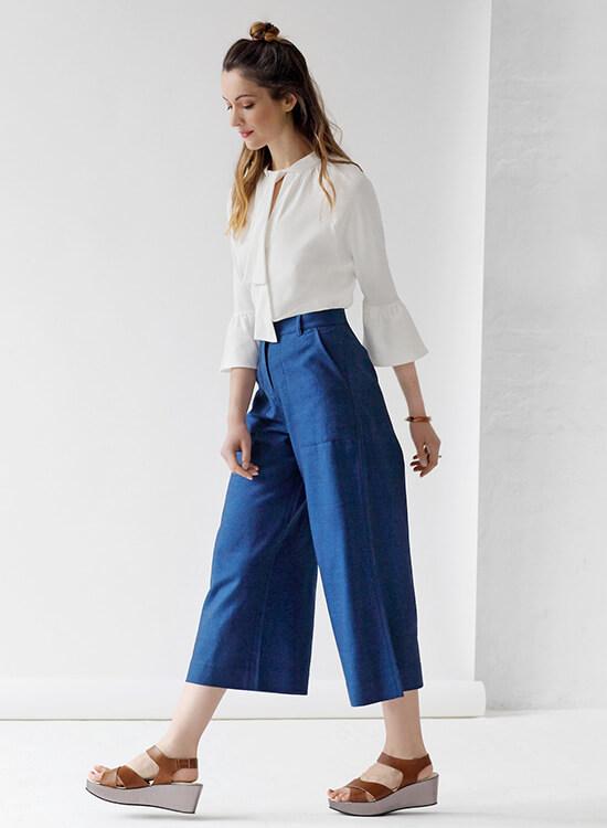 Frau in blauer Culotte und weißer Bluse