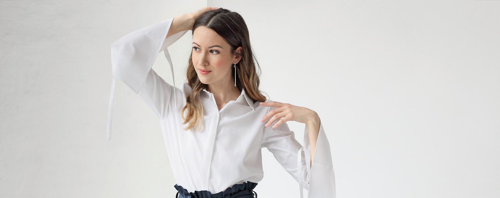 Frau in weißer Bluse vor Wand