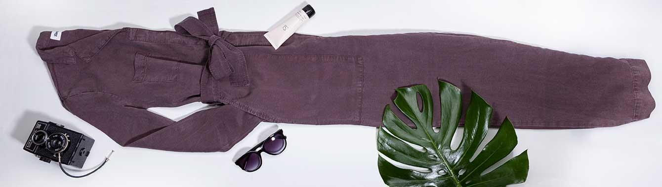 Jumpsuit liegt mit Accessoires gefaltet auf weißem Hintergrund